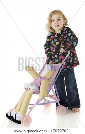 An adorable preschooler pushing her dolly in a toy umbrella stroller.  On a white background.