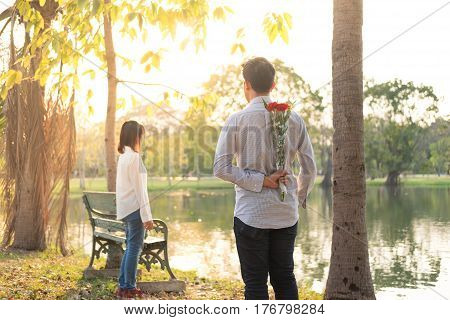 back view young man being giving bouquet red flower for girlfriend in public garden sunset time have small lake background