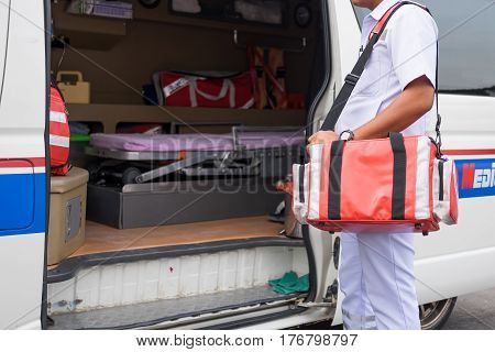 male nurse carry nursing bag standing beside ambulance prepare for helping people
