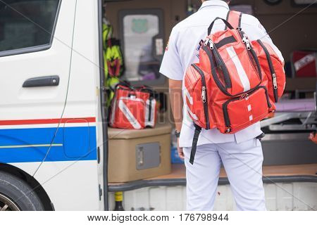 male nurse carry nursing bag on his back standing beside ambulance prepare for helping people