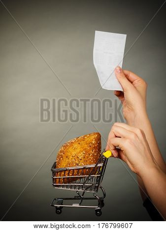 Buying gluten food products concept. Woman hand holding shopping cart trolley with small piece of bread and receipt bill