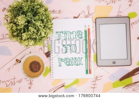 Tea cup, ebook and notebook with an inscription: time to relax