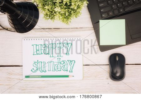 Workspace notebook and inscription in a scratchpad: happy sunday