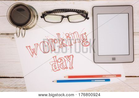 Coffee cup, notebook and ebook with an inscription: working day