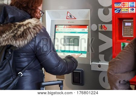 Naples Italy - March 13 2017: Ticket Machine in Central Station a lady buys a train ticket for his trip typing on the device monitor.