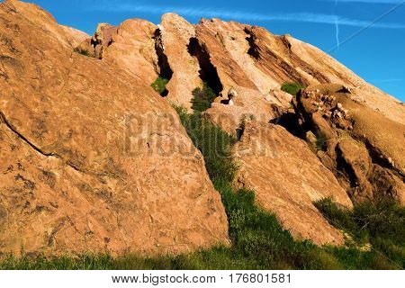 Rocks uplifted from the San Andreas Fault surrounded by lush green grasslands during spring taken at Vasquez Rocks in the Mojave Desert, CA