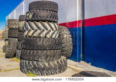 Stack Of Worn Rubber Tires Stacked On Side Of Building