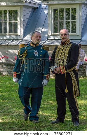 Saint Petersburg, Russia - may 15, 2016: Actors demonstrate vintage clothing 19 century in the Park. Two older men in old uniforms pose in front of green meadows and facade of the old house