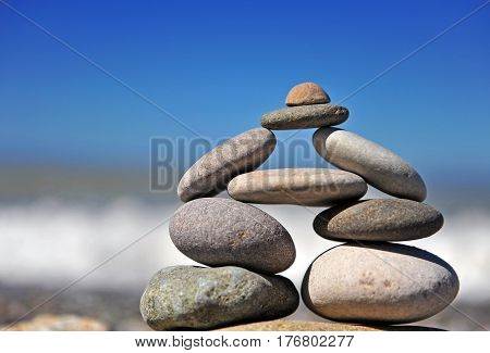 Stones pyramid standing at the sea with blue sky on background