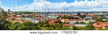 Panorama of Vilnius from top of mountain of Gediminas Tower. Red rooftops of old town & modern business building of glass and concrete. On horizon is television tower. Lithuania