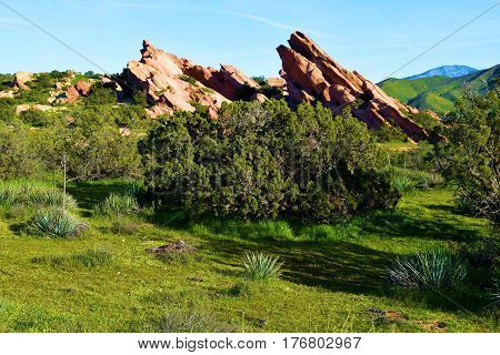 Rocks uplifted from the San Andreas Fault surrounded by a lush green chaparral woodland during spring taken at Vasquez Rocks in the Mojave Desert, CA
