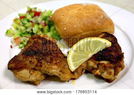 Oven grilled chicken thighs with a chopped salad, slice of lemon and bread roll