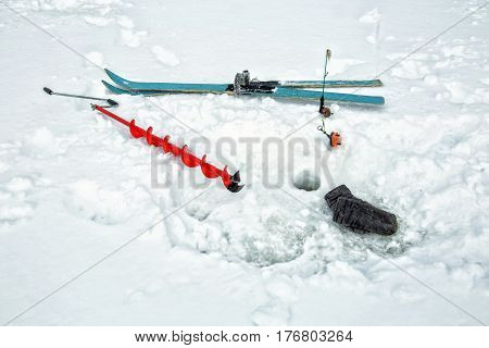 Things of a fisherman in the snow. Mittens auger skis and fishing rods
