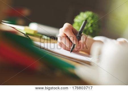 Side view of girl's hand sketching in spiral notepad placed on wooden desktop with blurry coffee cup and decorative plant