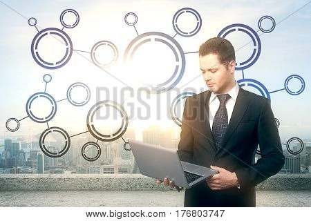 Handsome young businessman on roof top using laptop with abstract digital pattern. Bright city background. Tech concept