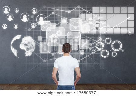 Back view of businessman in dark interior looking at wall with digital financial charts icons and globe. International business concept. 3D Rendering