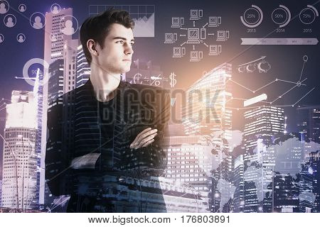 Handsome young businessman with folded arms on night city and forex chart background. Double exposure. Finance concept