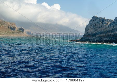 The rocky coast of the Mediterranean sea against the blue sky and clouds.