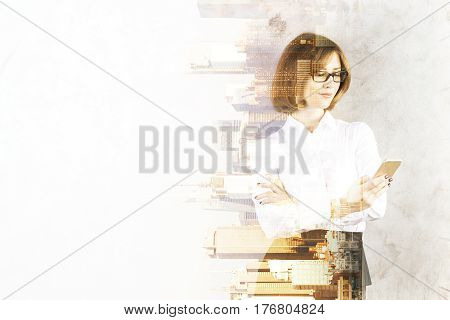 Portrait of attractive young woman using smartphone on abstract sideways city background with copy space and sunlight. Double exposure