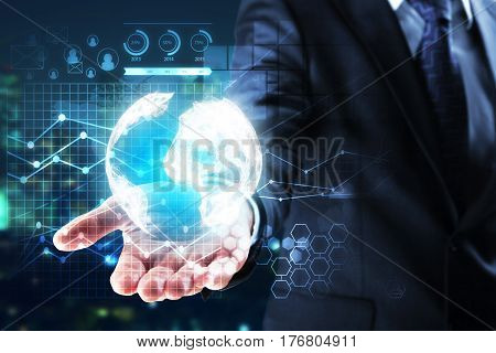 Businessman's hand holding abstract digital earth with business charts on blurry city background. Global business concept