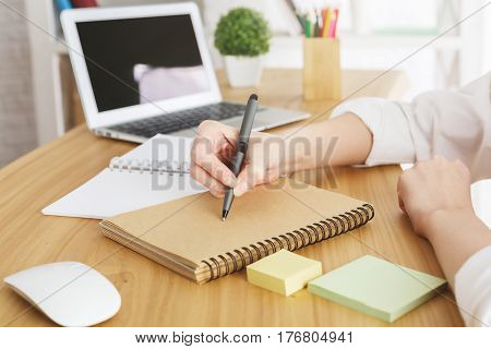 Close up of businesswoman's hands writing in spiral notepad placed on wooden desktop with blank laptop screen. Paperwork concept. Mock up