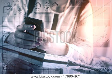 Close up of female hands using smartphone with digital business charts at workplace. Accounting concept