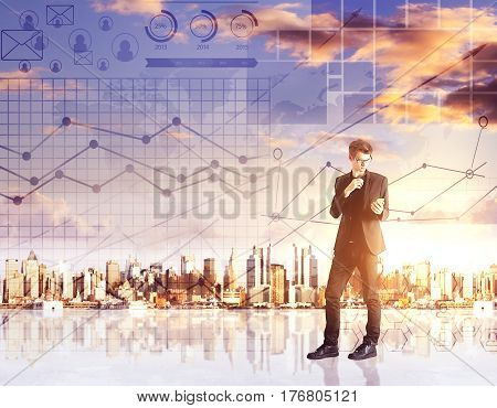 Handsome young businessman using smartphone on abstract city background with digital financial charts. Online business concept