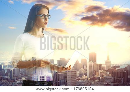 Thoughtful young girl using laptop on bright city background. Double exposure. Communication concept