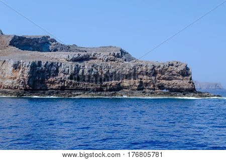 The rocky coast of the Mediterranean sea against the blue sky on a clear summer day
