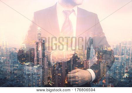 Confident young businessman in suit and tie on creative city background. Double exposure. Future concept
