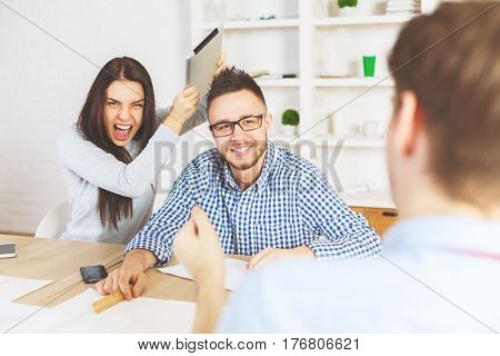 Young girl jokingly hitting guy with tablet while they are being interview for a job