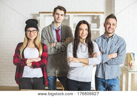 Front view of attractive cheerful caucasian people with folded arms in modern office. Teamwork concept