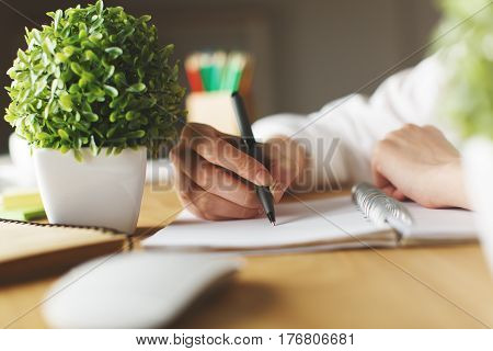 Close up of female hands writing in spiral notepad placed on wooden desktop with decorative plant and other items. Education concept