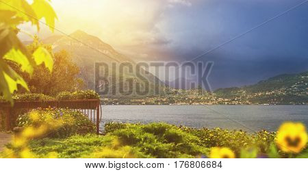 Beautiful toned panoramic waterscape of coastline of italian Varenna city with mountains on background leaf on foreground and dramatic sky before the rain