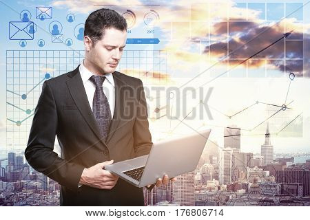 Handsome european businessman using laptop on bright city background with financial charts. Online finance concept