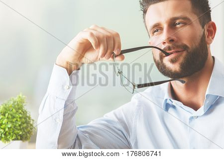 Close up portrait of handsome white male with glasses on blurry background with decorative plant. Thoughts concept