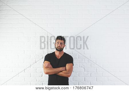 Portrait of handsome thoughtful young man with folded amrs looking up on white brick background
