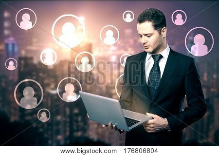 Businessman using laptop with abstract HR icons on blurry city background. Recruitment concept