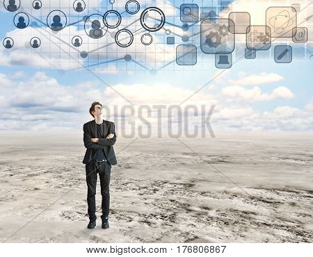 Young businessman with folded arms looking at sky with digital business charts. Financial growth concept