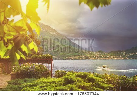 Beautiful toned waterscape of coastline of italian Varenna city with focus on mountain on background leaf on foreground trees and dramatic cloudy sky before the rain