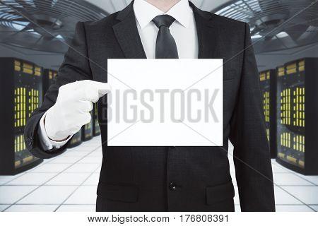 Businessman holding blank business card in server room. Mock up 3D Rendering