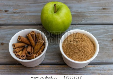 Green apple and cinnamon sticks and cinnamon powder in white porcelain bowls.
