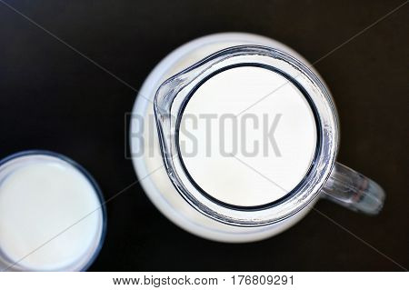 White Milk In The Glass With The Jug On The Black Background
