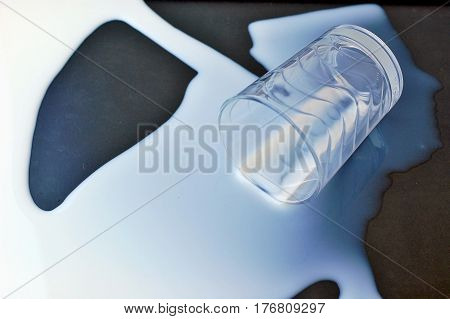 White Spilled Milk With The Glass On The Black Background