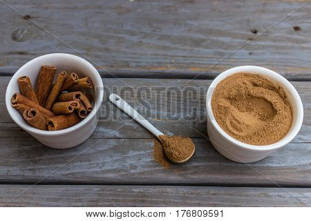 Cinnamon sticks and cinnamon powder in two white porcelain bowls and white porcelain teaspoon between them with cinnamon powder.