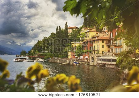 Beautiful cityscape with a Como lake coastline of italian Varenna city with colorful building big trees and dramatic sky before the rain with a bokeh flowers on foreground