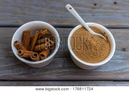 Cinnamon sticks and cinnamon powder in white porcelain bowls and teaspoon.Top view.