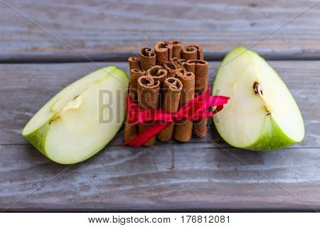 Two green apple slices and a pile of cinnamon sticks tied with a red ribbon.