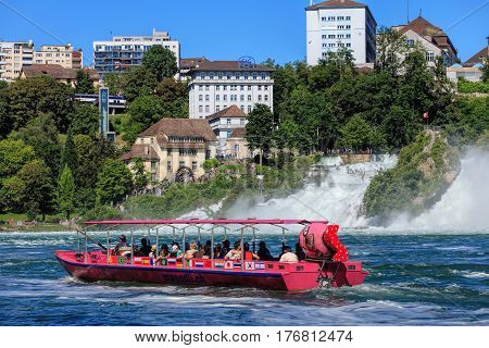 Neuhausen am Rheinfall, Switzerland - 22 June, 2016: people in a boat at the Rhine Falls, selective focus on the main subject with somewhat blurry background. The Rhine Falls is the largest plain waterfall in Europe.