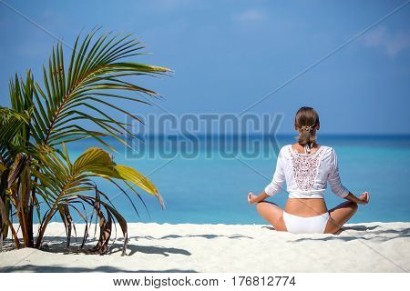 Young woman practicing yoga meditation on the beach facing the ocean near a palm tree on Maldives.